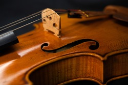 A close up shot of a professional tan varnished violin focused on the bridge, strings, and f hole.