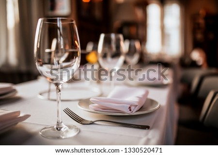 Photo of A close up shot of a restaurant table set up with tableware and wine glass. Concept of dining, hospitality and catering. Horizontal image with free space for text.