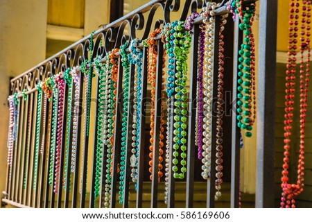 A close-up shot of a row of mardi gras beads hanging from a balcony in the French Quarter of New Orleans, There is a tiny lizard perched on the railing.