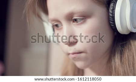 A close-up shot of a rushing plan portrait of a serious pensive and detached girl who is 10 years old in large white headphones indoors. Side look