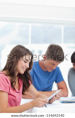 A close up shot of a smiling girl using her tablet pc with her friends studying beside her