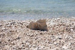 A close-up shot of a stone with a pictogram from numbers on the beach