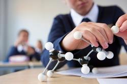 A close up shot of a student's hand in school uniform assembling an atom model at a desk.
