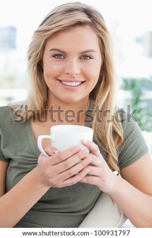 A close up shot of a woman, with a mug in her hands in front of her as she smiles and looks in front of her.