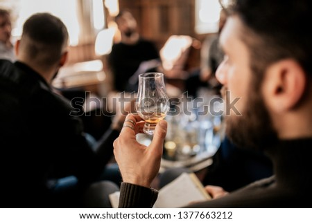 A close up shot of a young european man tasting Japanese whisky. Concept of fine alcohol. Master class and degustation of whisky.  Foto stock ©