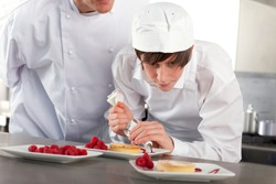 A close up shot of a young trainee decorating dessert in a kitchen.