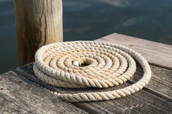 A close up shot of an old coiled nautical rope on a wooden pier next to the water in Mystic, Connecticut