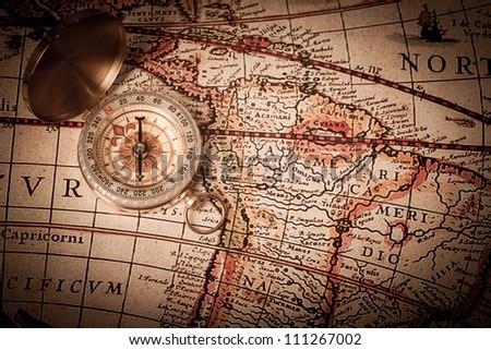 A close-up shot of an open brass compass on a antique, 1920's map.