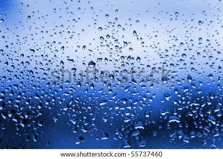 A close up shot of blue water droplets on a glass window pane.