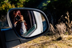 A close-up shot of the reflection of an unrecognizable young Caucasian redhead female photographer holding a DSLR photo camera in the rearview mirror of a moving car