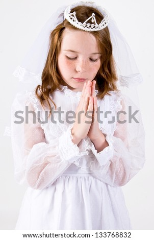 A close-up, shot straight on, of a young girl praying in her First Communion Dress and Veil