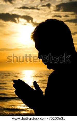 A close up silhouette of a man with his head bowed in prayer at the ocean.