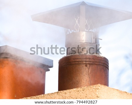 A close-up view of a clay lined fireplace chimney with white smoke and steam pouring through the top from the furnace on a cold winter day rising into the blue sky and white clouds in the background.