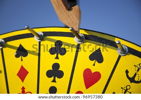"""A close up view of a Crown and Anchor """"Wheel of Fortune"""" game horizontal view."""