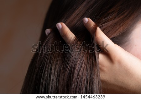 A close up view of a gorgeous young brunette lady with lacquered nails. Combing her fingers through the straight, sleek and conditioned hair. Copy space on the left.