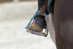 A close up view of a horse riders stirrup