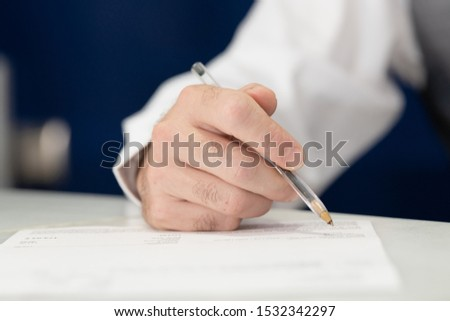 A close-up view of a man holding a pen while he writes on a sheet of paper.