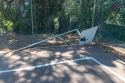 A close up view of a old  damaged basketball hoop that has fallen down on an abandoned tennis court