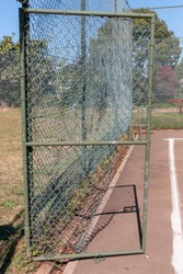 A close up view of a old damaged gate on an abandoned tennis court