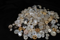 A close up view of a pile of vintage shell, bone, and celluloid buttons.