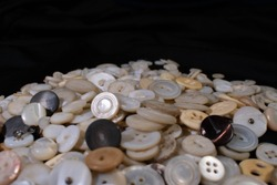 A close up view of a pile of vintage shell, bone, and celluloid buttons with soft focus.
