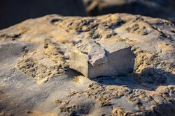 A close up view of a small stack of rocks shot at sunset.  There are two smaller rocks, one square and one rectangular stocked on top of a large, well worn boulder.  Lots of room for copy space.