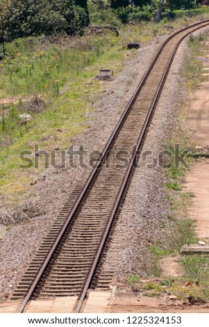 A close up view of a straight metal and concrete railway lines that is curving at the end  #1225324153
