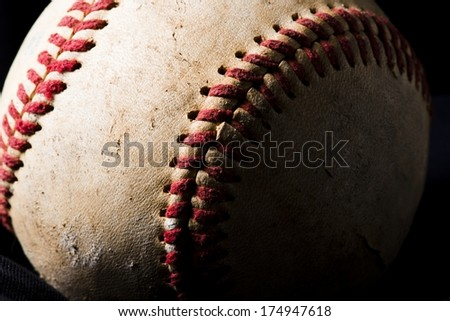 A close up view of a weathered baseball.