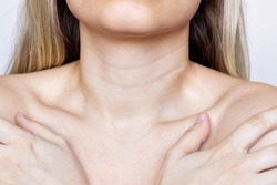 A close-up view of a young woman's neck and chest. Lines on the neck. Wrinkles, age-related changes, rings of Venus