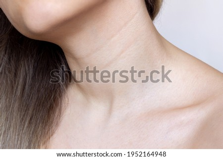 A close-up view of a young woman's neck and chest. Lines on the neck. Wrinkles, age-related changes, rings of Venus, goosebumps Foto stock ©