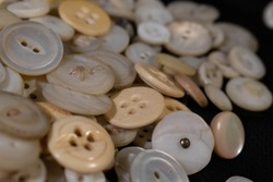 A close up view of an assortment of shell, celluloid, and bone buttons.