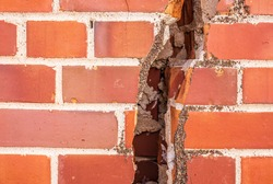 A close up view of an extremely large crack in a brick wall that is several inches wide