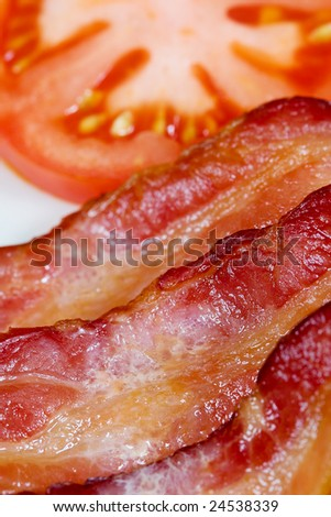 A close up view of bacon with a tomato in the background