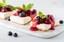 A close up view of cheesecake squares topped with cherry sauce and blueberries and garnished with mint.