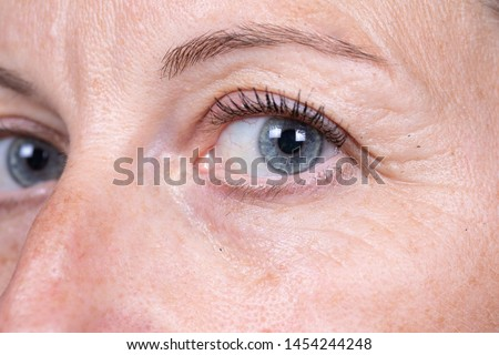 A close up view on the blue eye of a Caucasian woman in her early forties. Details of the laughter lines and crow's feet. Natural aging of the human face. Stock photo ©
