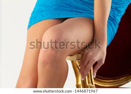 A close up view on the bronzed legs of a stylish Caucasian woman wearing a short blue dress, sitting on an armchair in a flirtatious manner.