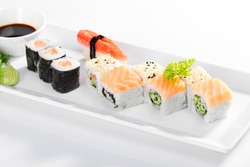 A close view of different sushi types with soy sauce, wasabi and dill on a white serving platter isolated on a white background.