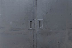 A closed black iron door.