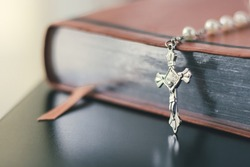 A closed brown bible with silver page lining is set on a black shiny desktop. A silver and pearl rosary necklace is placed on the bible. The cross pennant rests on the table in front of the bible.