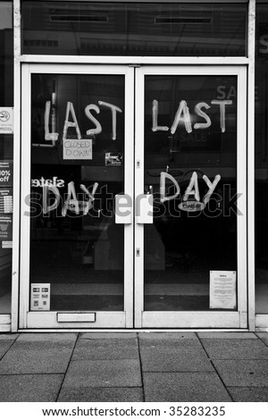 A closed down shop with the words Last Day wrtten on the glass doors