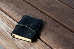 A closed leather bound black journal outdoors on table, wrapped with cord  with copy space.