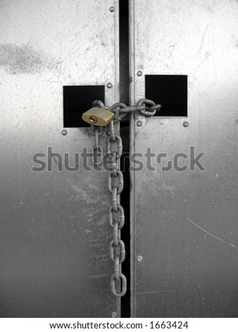 A closed silver metallic gate locked with an iron chain and padlock