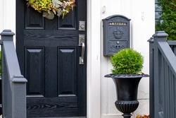 A closed solid wood black front door of a house. There's a black mailbox hanging on the white exterior wall. There's a flower pot with a green hedge. The door has a colorful flower wreath.