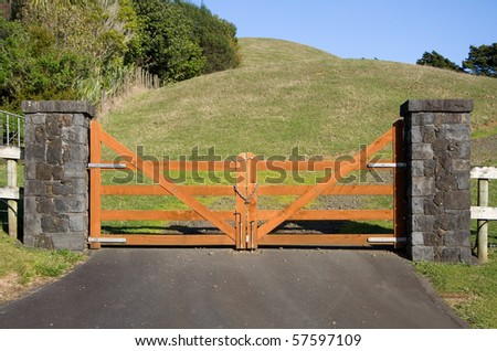 A closed wooden gate on a vacant paddock in the New Zealand countryside
