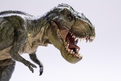 A closeup and side profile view of a fierce Tyrannosaurus Rex resin figurine, isolated on a clean white background.