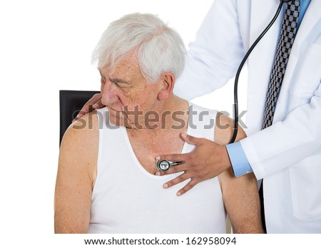 A closeup cropped portrait of a doctor performing heart lungs chest physical exam  listening with stethoscope on an elderly senior mature man sitting on black chair, isolated on a white background.  - stock photo