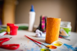 A closeup horizontal shot of a yellow cardboard tube on a background of painting materials for children