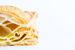 A closeup image  of puff pastry in the incision with blown large crunchy layers of golden brown crust on top visible. Located on the left side on white background with copy space.