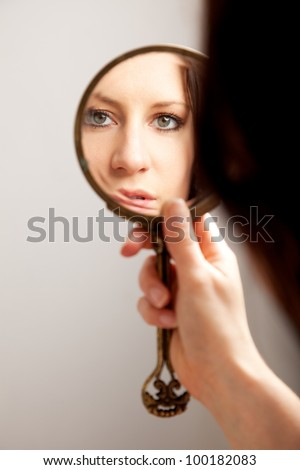 A closeup mirror reflection of a woman's face, selective focus