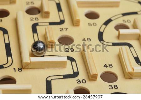 A closeup of a ball bearing navigating a wooden maze